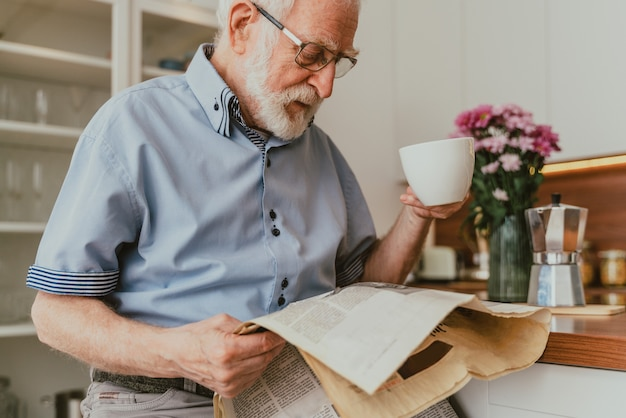 Senior man ontspannen thuis, krant lezen en ontbijten