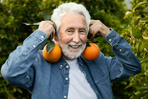 Senior man oogsten sinaasappelbomen