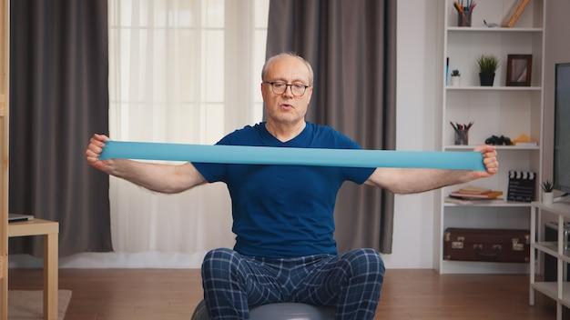 Senior man op balans bal training met weerstandsband. bejaarde gepensioneerde gezonde opleiding gezondheidszorg sport thuis, fitness activiteit uitoefenen op oudere leeftijd