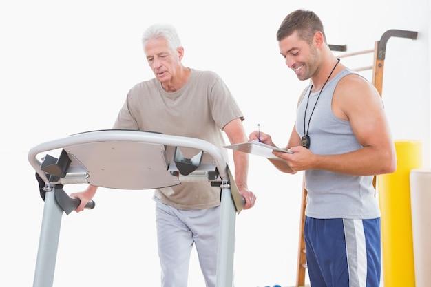 Senior man op de loopband met trainer