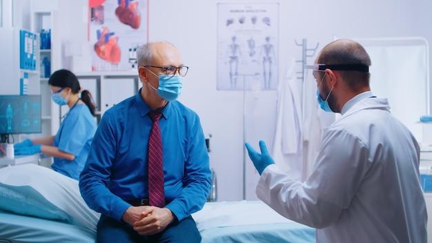Senior man op doktersafspraak tijdens covid-19 pandemie. patiënt met masker en arts in beschermende kleding. gezondheidszorgoverleg, medicinaal systeem. privé moderne kliniek
