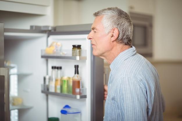 Senior man op zoek in de koelkast
