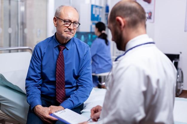 Senior man overleg met arts zittend op ziekenhuisbed in onderzoekskamer