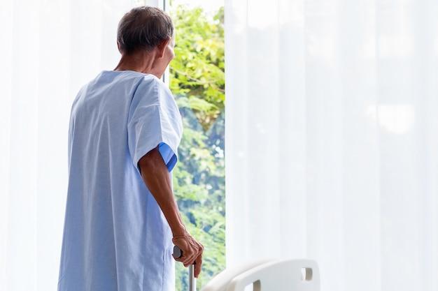 Senior man patiënt met wandelstok in het ziekenhuis kamer.