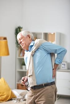 Senior man permanent in de woonkamer en hand op de onderrug terwijl hij pijn voelt