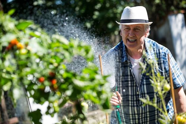 Senior man planten water geven met een slang