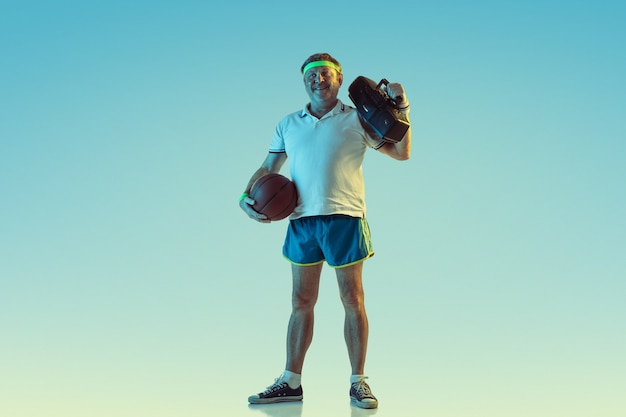 Senior man poseren prachtig in sportkleding met retro bandrecorder op kleurovergang muur, neon. kaukasisch mannelijk model in uitstekende vorm, sportief. concept van sport, activiteit, beweging, gezonde levensstijl.