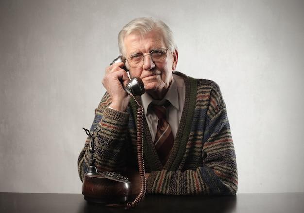 Senior man praten op een klassieke telefoon