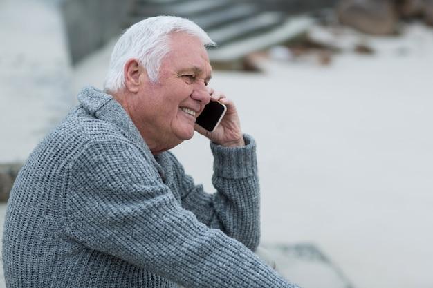 Senior man praten op mobiele telefoon