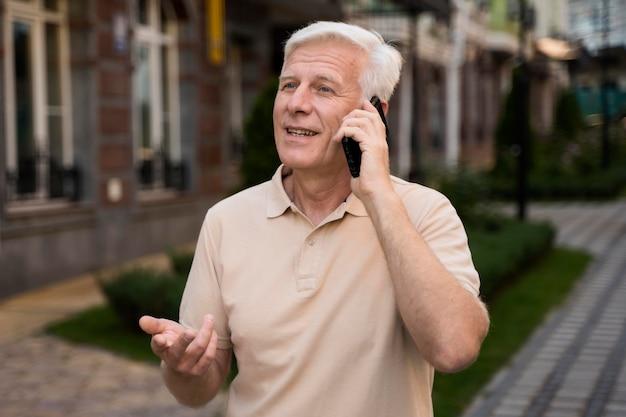 Senior man praten over smartphone terwijl hij in de stad is