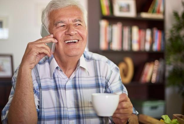 Senior man praten over zijn mobiele telefoon