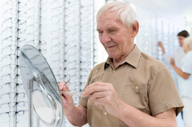 Senior man probeert een nieuwe bril