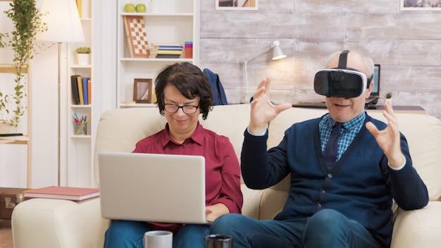 Senior man probeert een vr-headset in de woonkamer terwijl zijn vrouw een laptop naast hem gebruikt. modern oud paar dat technologie gebruikt