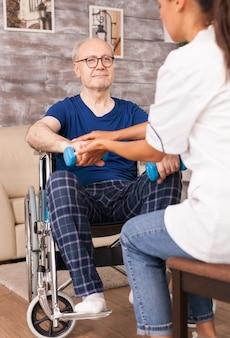 Senior man probeert zijn hand op te steken met halters