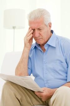 Senior man problemen met het gezichtsvermogen tijdens het lezen van een krant thuis