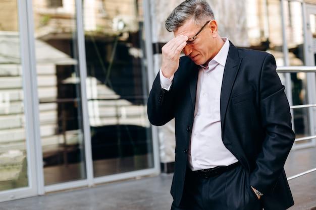 Senior man raakt zijn hoofd door zijn hand. - concept hoofdpijn, afbeelding