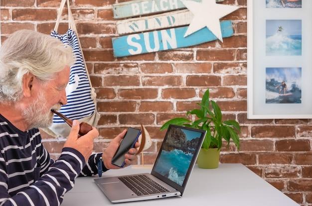 Senior man rookpijp met behulp van laptop en smartphone op wit bureau thuis. oudere witharige mensen genieten van technologie. bakstenen muur op de achtergrond en versieringen