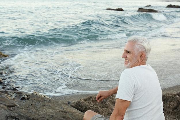 Senior man rust op het strand en bewondert de oceaan