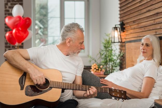Senior man serenading vrouw op valentijnsdag