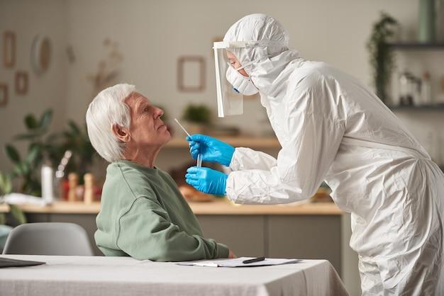 Senior man slaagt voor coronavirus-test met arts in beschermend pak die thuis een analyse maakt