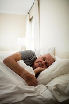 Senior man slapen in de slaapkamer thuis