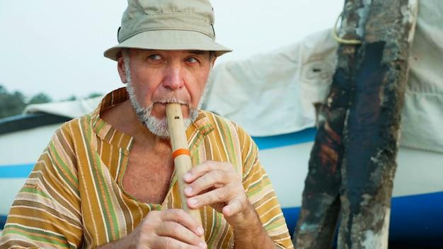 Senior man spelen bamboe fluit op het strand naast vissersboot
