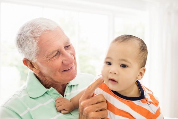 Senior man spelen met zijn kleinzoon thuis