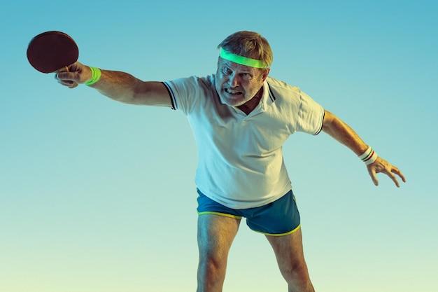Senior man tafeltennis spelen op verloop achtergrond in neon licht. blank mannelijk model in uitstekende vorm blijft actief, sportief.