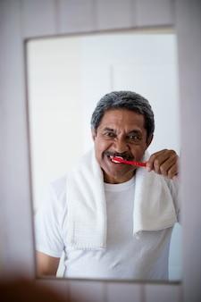 Senior man tandenpoetsen in de badkamer