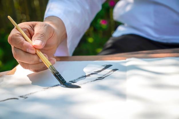 Senior man tekening bamboeboom door azië china penseel met aziatische streekstijl. hij zit in de ontspannende bamboektuin.