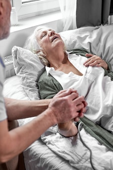 Senior man ter ondersteuning van haar zieke vrouw in het ziekenhuis, met haar hand. vrouw voelt zich slecht. gezondheid en geneeskunde concept