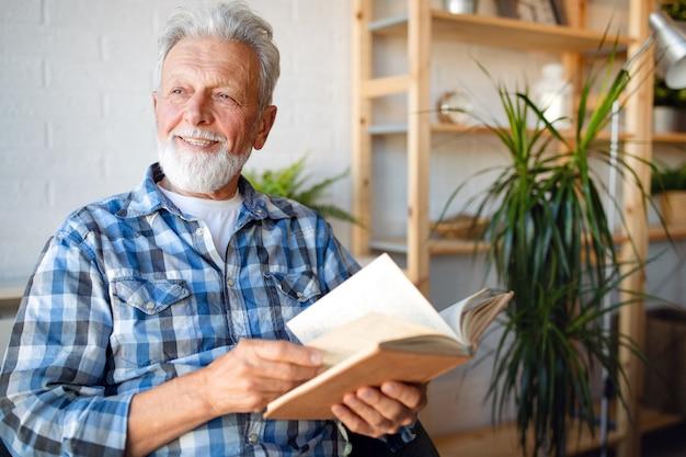 Senior man thuis boek lezen en genieten van pensioen, penison