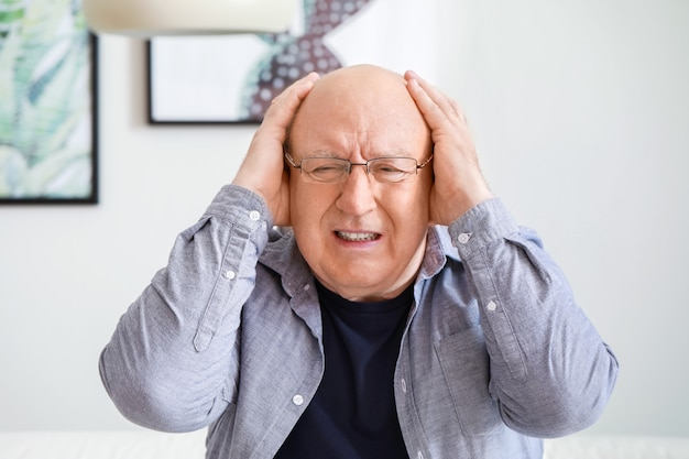 Senior man thuis hoofdpijn lijden