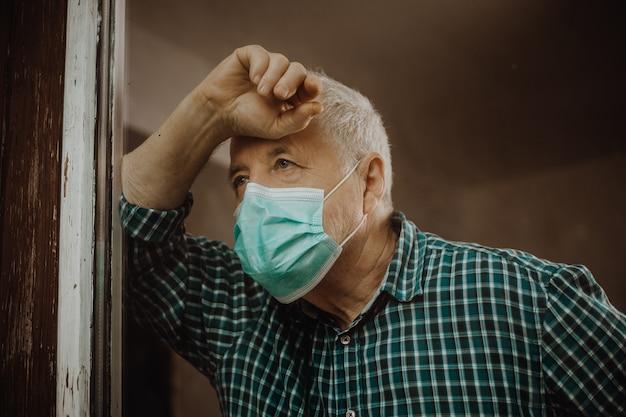 Senior man thuis in quarantaine geplaatst tijdens een coronavirus-pandemie, blijf veilig