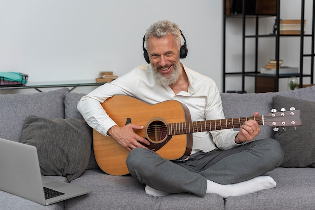 Senior man thuis op de bank met laptop om gitaarlessen te studeren