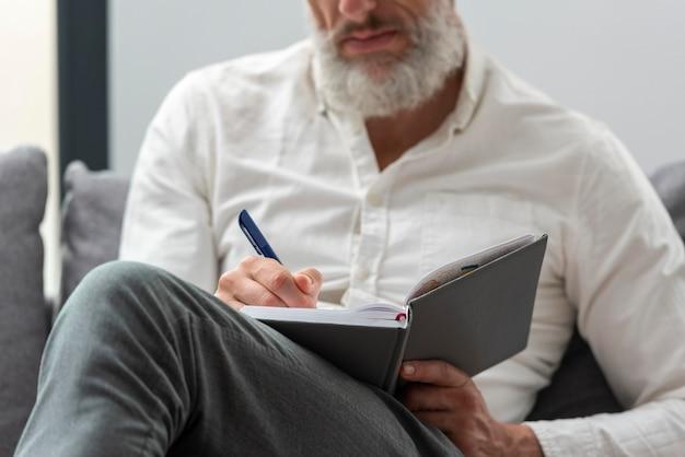Senior man thuis studeren en aantekeningen maken