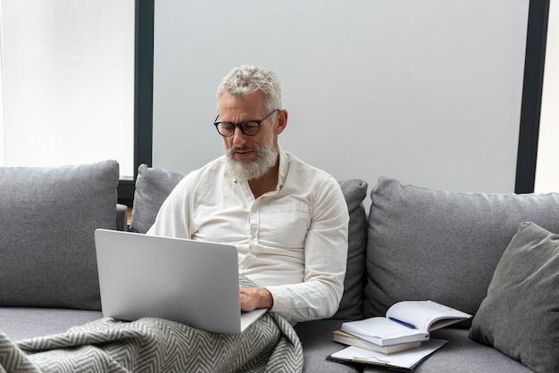 Senior man thuis studeren op de bank met behulp van laptop