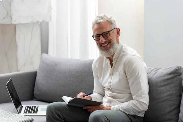 Senior man thuis studeren op laptop en aantekeningen maken