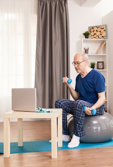 Senior man training biceps kijken naar online fitnessles