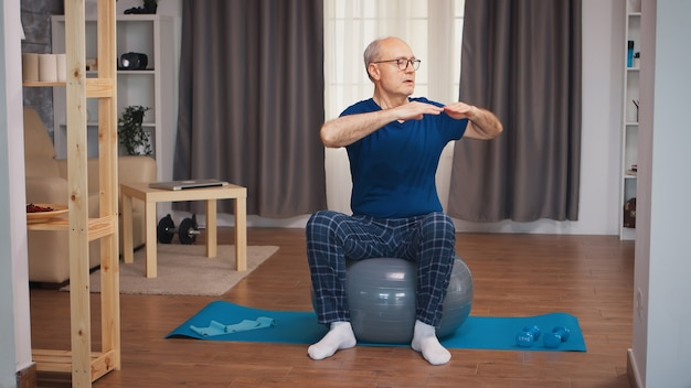 Senior man training op stabiliteit bal in woonkamer. bejaarde gepensioneerde gezonde opleiding gezondheidszorg sport thuis, fitness activiteit uitoefenen op oudere leeftijd