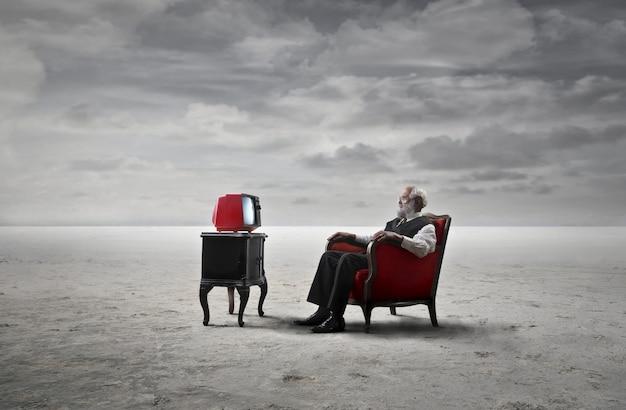 Senior man tv kijken vanuit een leunstoel
