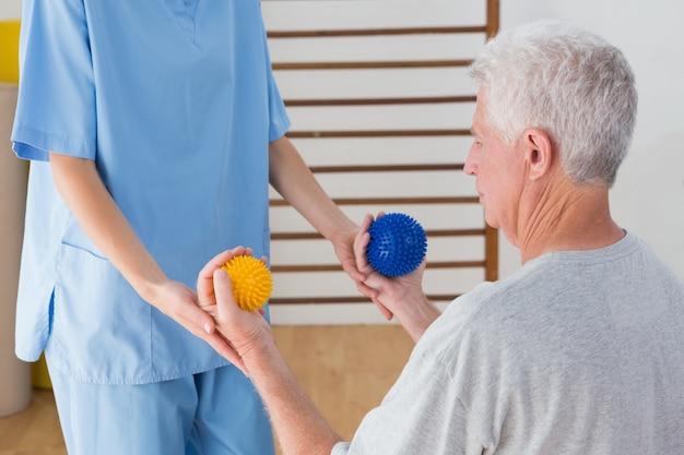 Senior man uit te werken met zijn therapeut