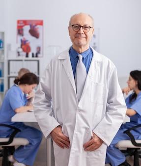 Senior man van de therapeut die voor de camera staat en het symptoom van een operatie analyseert