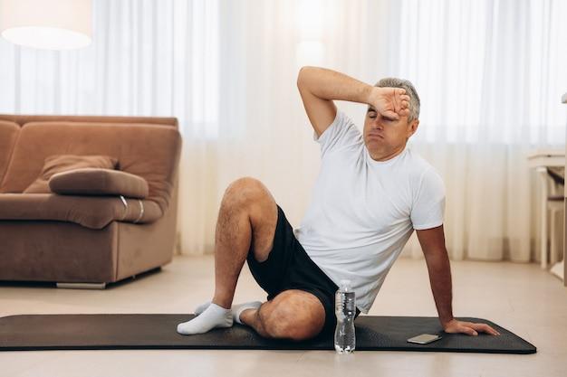 Senior man veegt zweet van zijn voorhoofd na zware thuistraining