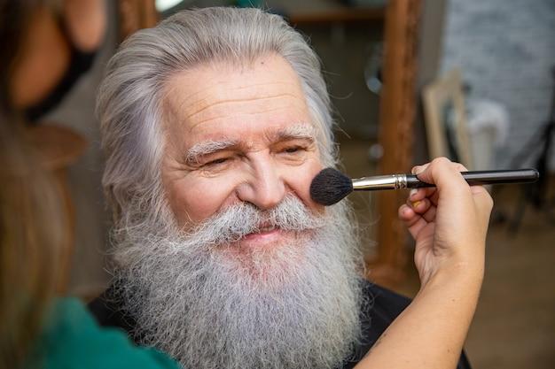 Senior man verandert in de kerstman in de schoonheidssalon. sinterklaas verzinnen