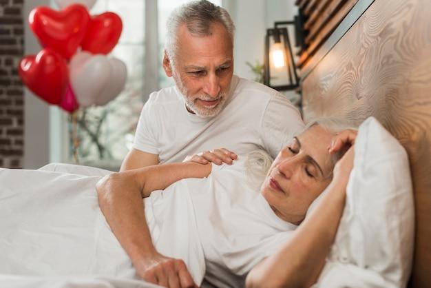 Senior man verrassende vrouw in bed