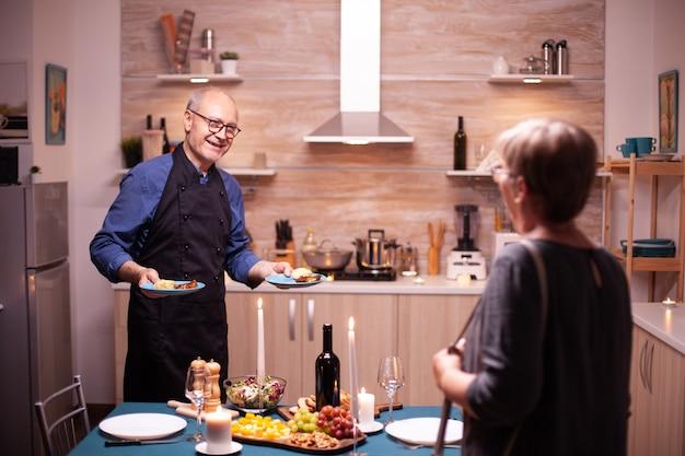 Senior man verrassende vrouw met romantisch diner en lekker eten. bejaard echtpaar praten, aan de tafel in de keuken zitten, genieten van de maaltijd, hun jubileum vieren in de eetkamer.