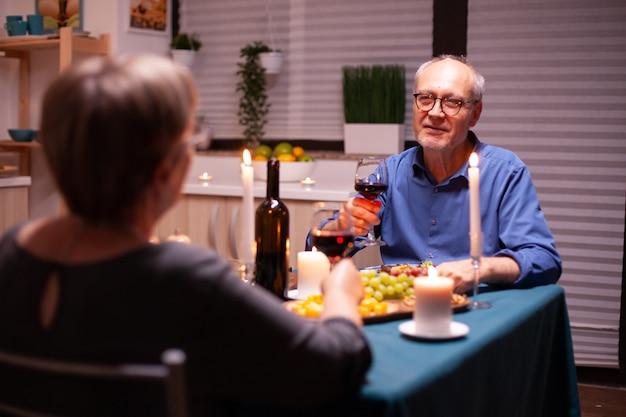 Senior man vertelt een verhaal aan zijn vrouw terwijl hij in de keuken viert met wijn en eten. senior koppel zittend aan tafel in de eetkamer, praten, genieten van de maaltijd, hun jubileum vieren in