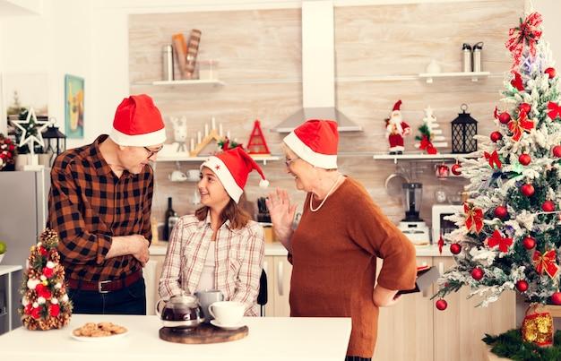 Senior man viert kerst met gelukkige nicht die haar geschenkdoos geeft