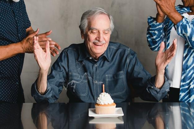 Senior man viert zijn verjaardag met zijn vrienden